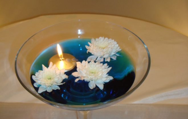 Champagne coupe with blue water floating candles and flower heads
