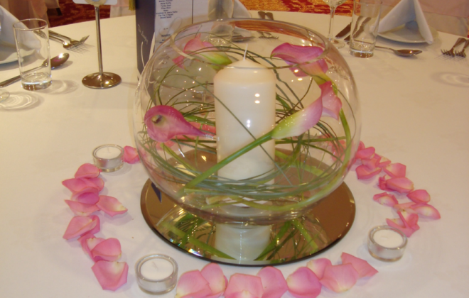 Fishbowl on mirrored tile with callas, bear grass and pillar candle